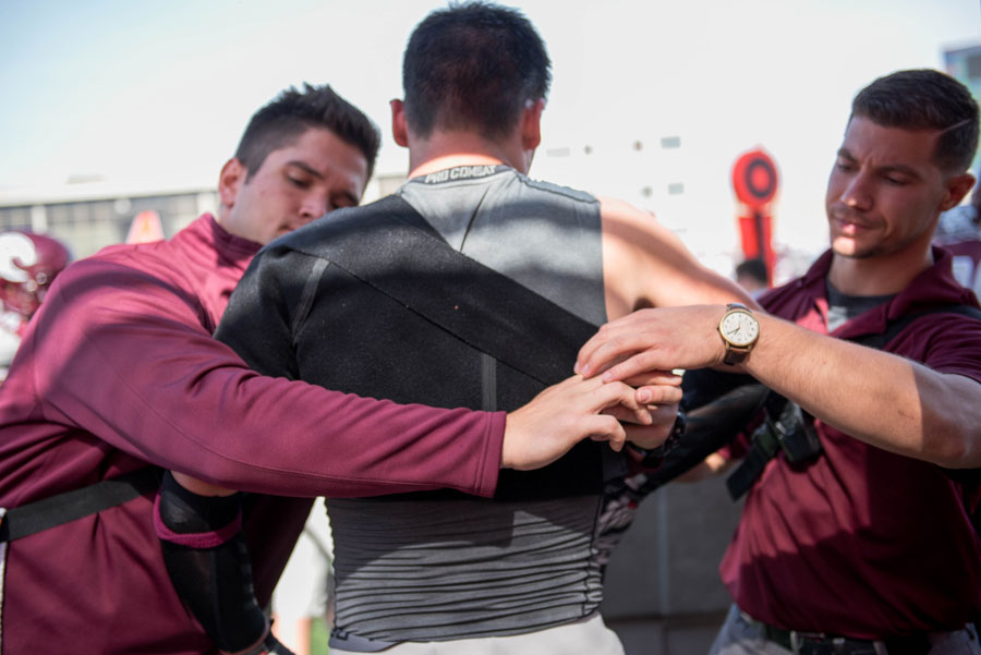 Athletic training staff members assist an Augsburg football player