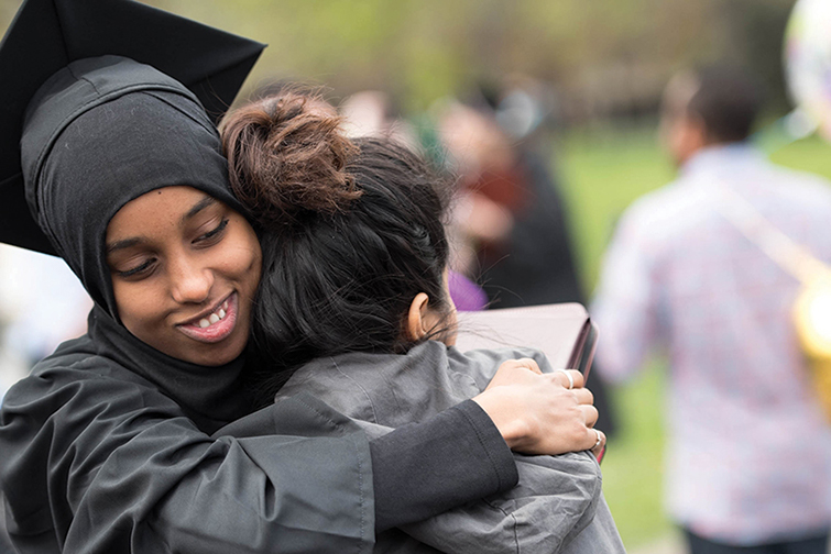 Students hug after a commencement ceremony