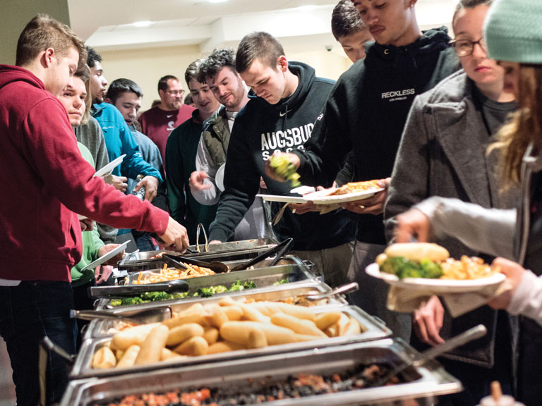 Augsburg student-athletes dish up food at a buffet