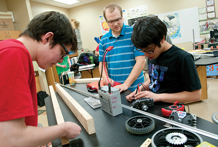 Augsburg alumnus Dan Forseth works with two students in a classroom