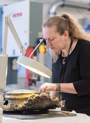 Juliane Derry '00 works on an artifact from Norway's national collection.