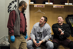 Minasie laughs with men's hockey players