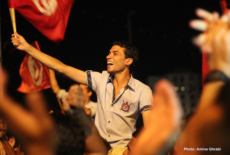 A Tunisian man waves a red flag