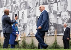 During a break, the 2015 Nobel Peace Prize laureates posed for photos in front of a three-story mural featuring their images along with dozens of other past laureates.