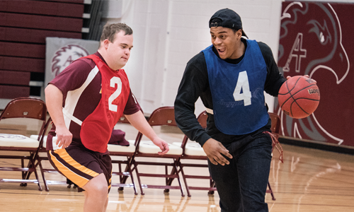 Augsburg student-athlete plays baskeball with Special Olympic athlete