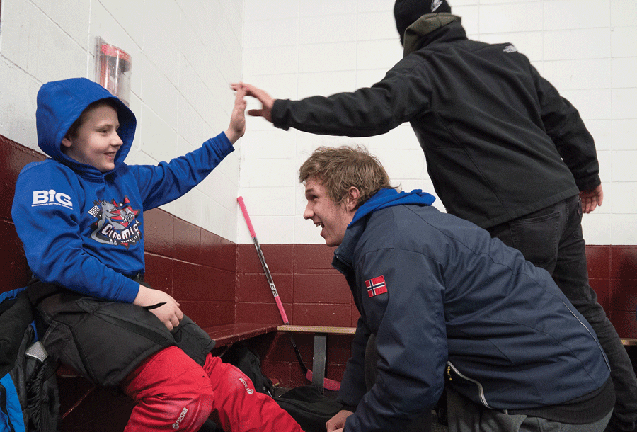 Kristian Evans '19 helps a member of the DinoMights Squirt team prepare for hockey practice. Players are 10 or 11 years old.