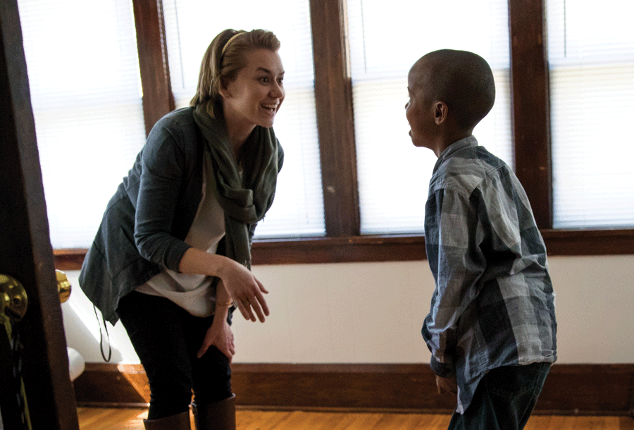 Katia Iverson '12 encourages a new arrival from a refugee family as he practices his English.