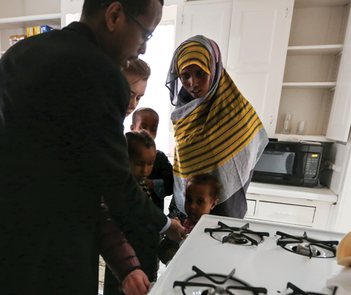 Ahmednor Farah and Iverson show a newly relocated refugee family how to ensure the gas burners on the stove are safely turned off.