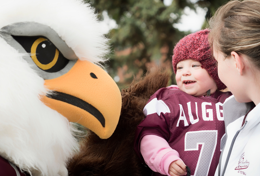 Child enjoys an interaction with Auggie the mascot