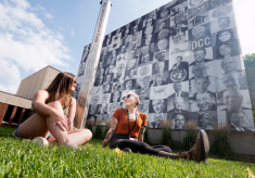 Students enjoy the sun in front of a mural hanging outside