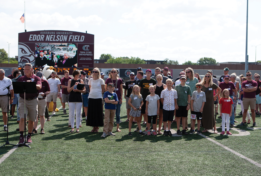 Friends and Family of pastor Dave Wold gather on the Augsburg field to see the unveiling of the Press Box