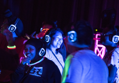 Students smiling while dancing at the silent disco