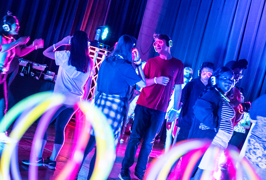 Students dancing with head phones on and neon colors surrounding them