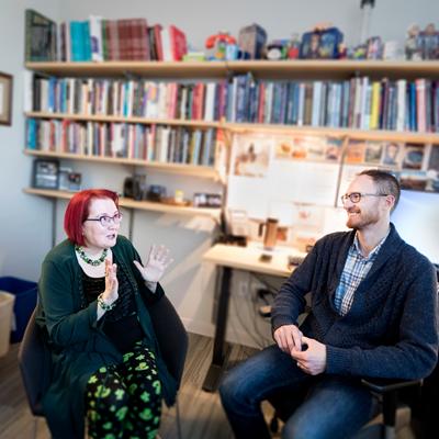 Professor Bridget Robinson-Riegler, left, talking to Assistant Professor Ben Denkinger in his office