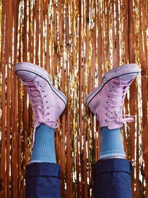 Feet in the air with pink Converse on