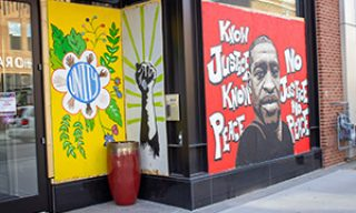 "George Floyd painting mural with words ""No justice No peace"""