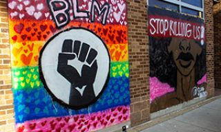 "BLM and Lgbtq flag mural along with a Black woman mural next to it with the words ""Stop killing us"""