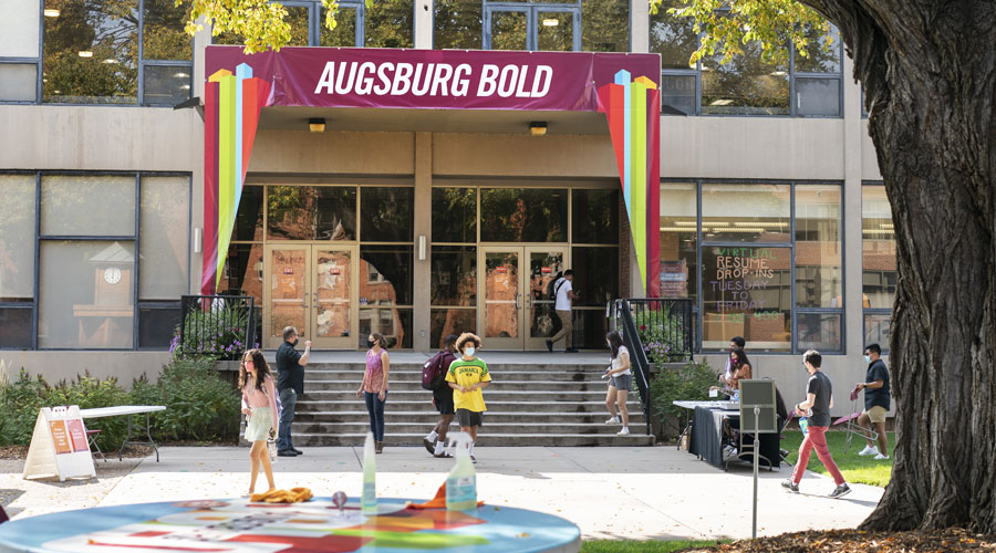 A sign across the balany over the Christensen Center stairs reads Augsburg Bold