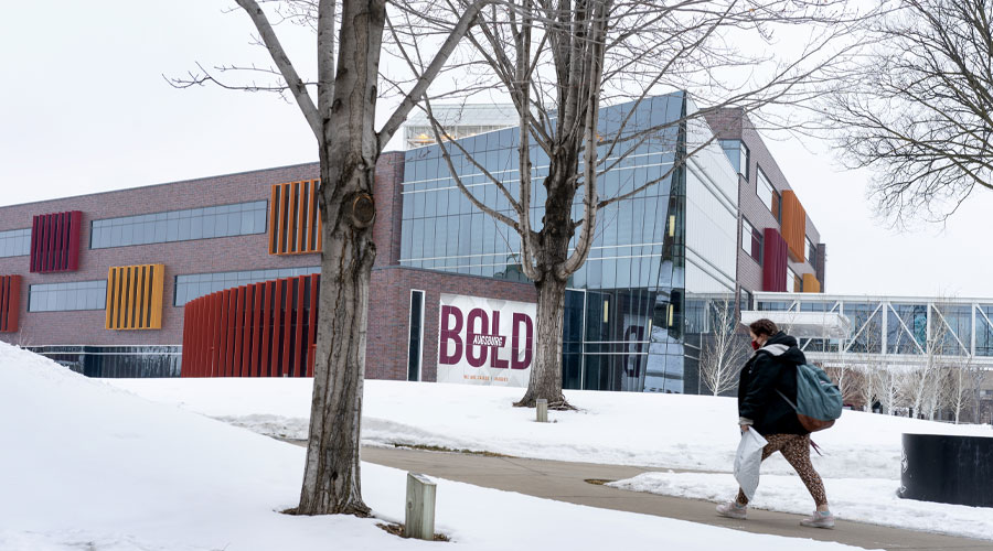A student walking on the sidewalk in front of Hagfors Center with snow on the ground.