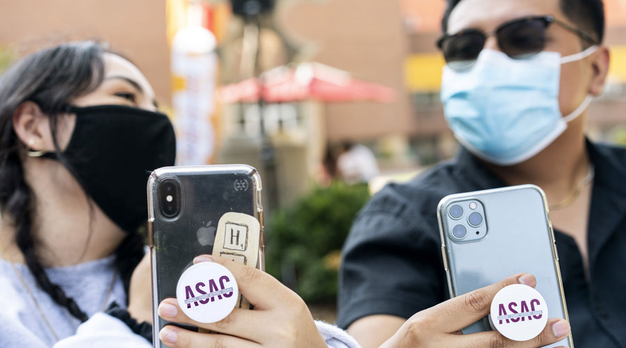 Two students with masks on holding their phones showing off their ASAC pop sockets