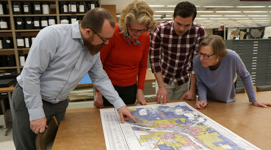 Four people standing around a table pointing at a map