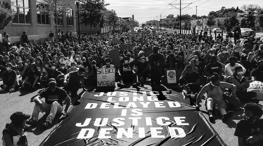 "A crowd of people peacefully protesting in a street. A sign laying on the ground says ""Justice Long Delayed is Justice Denied."""