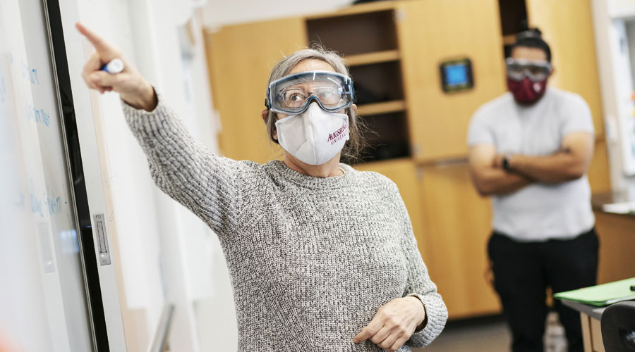 Professor teaching at the front of a science class with a face mask and eye wear on.