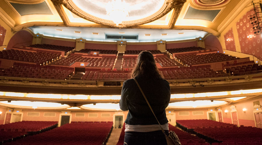 Student looking at the empty seats of a Minneapolis theater