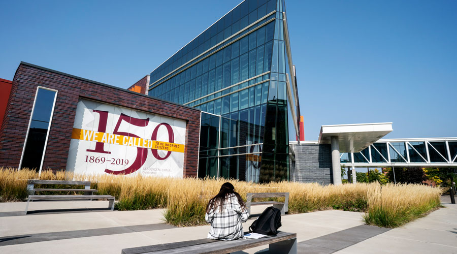 A student studying on a bench outside of Hagfors Center with a clear blue sky