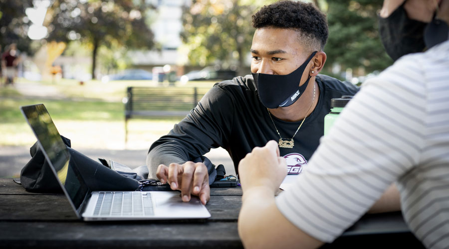 Student with mask on working on his computer