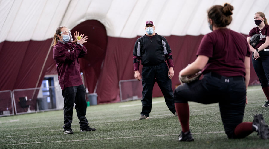 Coach Mel Lee coaching with a mask on in the dome