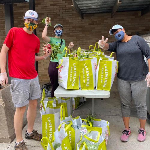 Three people with bags of groceries