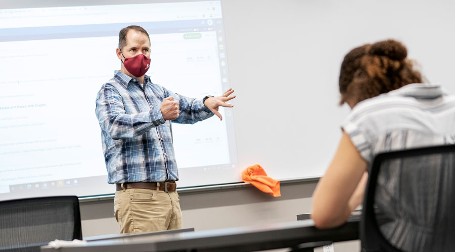 Sociology professor, Tim Pippert teaches in front of a class. He is wearing a face covering for COVID-19 protocal and safety.