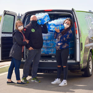 Avan full of bottles of water with Bethany Johnson (on the left, standing with each other) Husband, David Chall Daughter, Olivia Chall (on right) in front of the van.