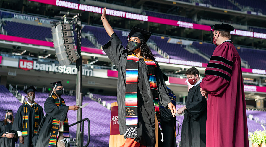 A student walks across the stage during Augsburg's in-person commencement