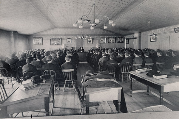 Georg Sverdrup and Sven Oftedal, speak at a gathering of students in the first Old Main building 1897.