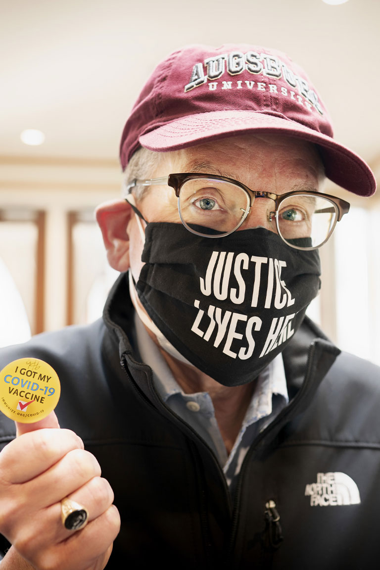 """Augsburg President, Paul C. Pribbenow holding his """"I Got My COVID-19 Vaccination"""" sticker. His face mask says """"Justic Lives Here""""."""