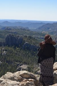 Female student standing on top of rocks at the peak of Black Elk Peak looking over the Black Hills.  She is wearing a black and white shirt, black sweater and maroon hijab.