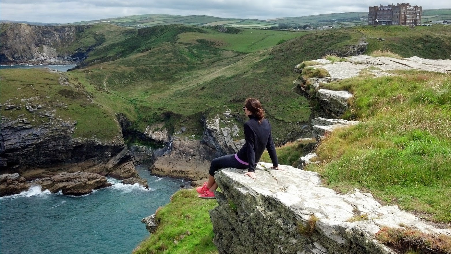 A woman sits atop a cliff in Cornwall, England. She is looking out over the ocean and the rolling hills of the English countryside. At this site she is experiencing the natural elements of the wind in her face, the ocean mist, the solid stone of the cliff, and the warmth of the sun. –photo credit K.McHale