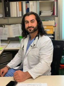 alum Hoshmand Las, PA-C sits in his white coat and scrubs in his office
