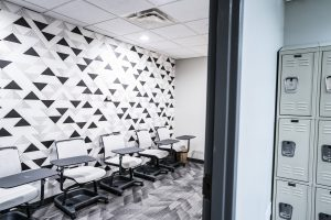 Geometric triangle black and white wallpaper on left hand wall. Moveable desks line left wall.