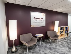 Reception area featuring two lobby chairs against a maroon wall with Augsburg University metal artwork. Chairs are framed by floor lamps
