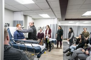 Students look onward as instructor demonstrates ENT exam