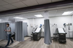 Clinical skills lab room showing two exam tables framed by two grey curtains