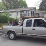 People in truck bed on the way to garden