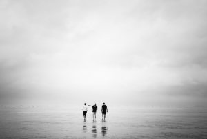 three people walking on cloudy beach