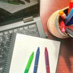 colorful pens on notebook near open laptop