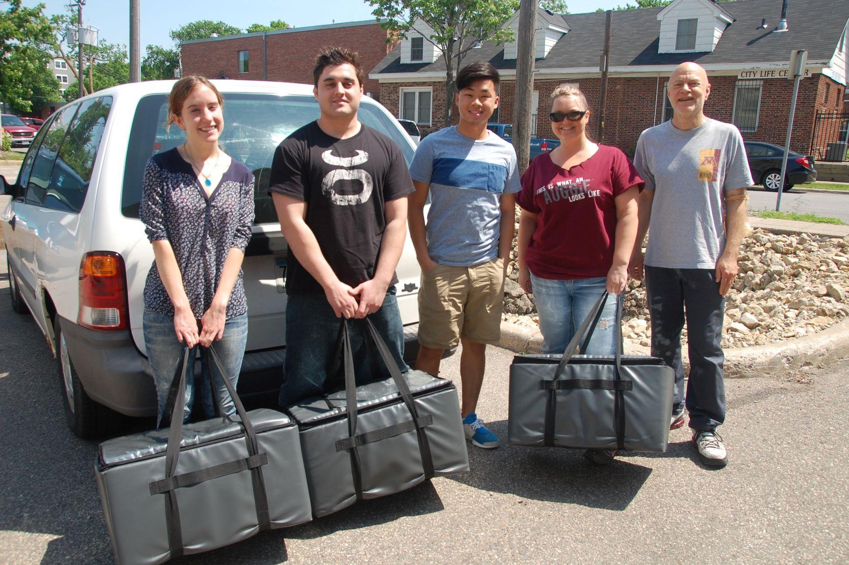 Students holding meal packs behind van