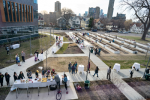 An aerial view of the Augsburg Community Garden. A table in the foreground has food on it, and people are lining up to serve themselves.