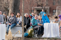 Ten people in diverse garb sit on the edges of raised garden beds or at tables. Some are eating food, others are looking ahead with attentive gazes.